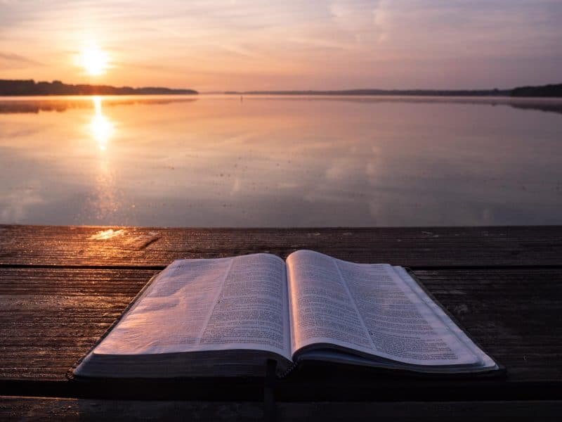 Bible in sunset by water (Which was the first the Bible or the Quran?)